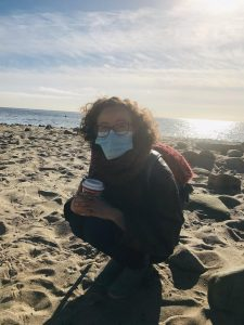 Sammy at the beach with a mask on and a coffee. Life makes sense with a coffee and a beautiful view.